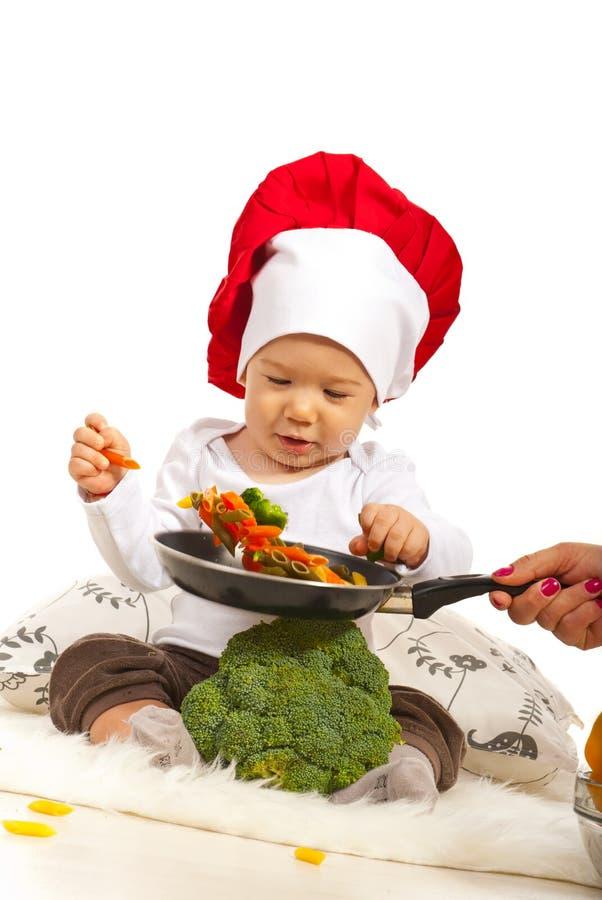Szefa kuchni dziecko bierze makaron obraz royalty free