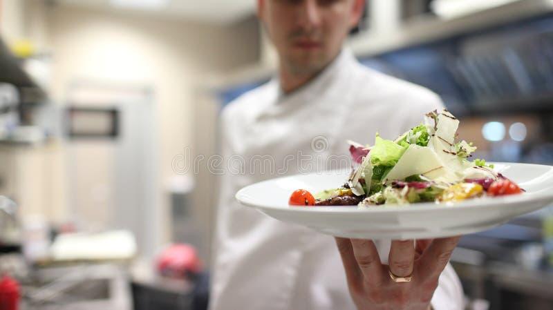 Szefa kuchni garnirowania sałatki w kuchennym garnirowaniu ich sałatki zdjęcie stock