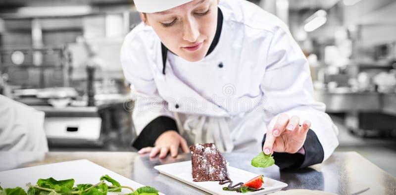 Szefa kuchni kładzenia mennica z jej czekoladowym tortem fotografia royalty free
