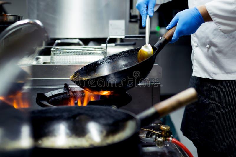 Szefa kuchni kucharstwo z płomieniem w smaży niecce na kuchennej kuchence fotografia stock