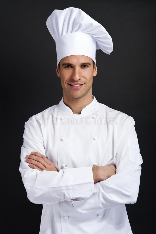 Szefa kuchni kucharz ono uśmiecha się z kapeluszową holdinf łyżką przeciw ciemnemu tłu obraz royalty free