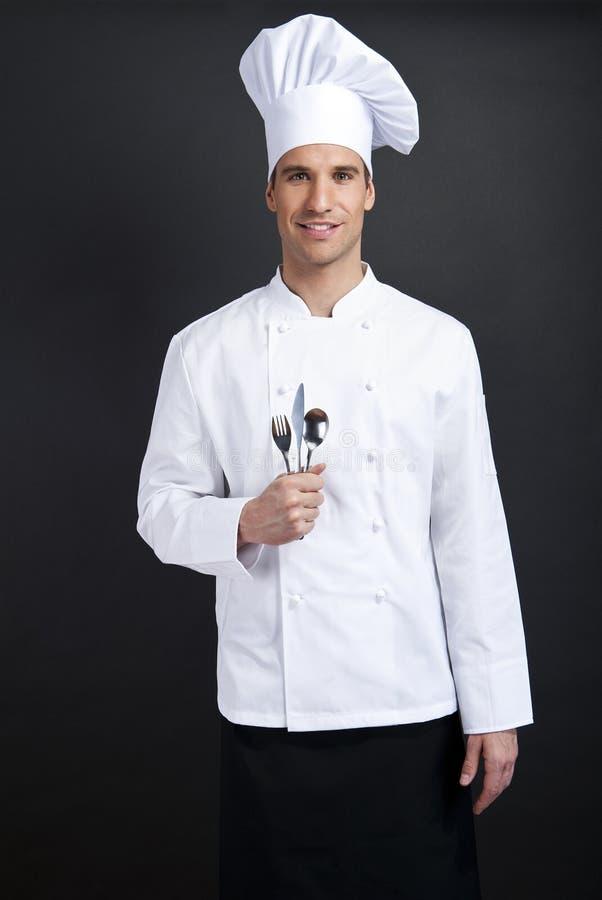 Szefa kuchni kucharz przeciw ciemnemu tłu obrazy stock