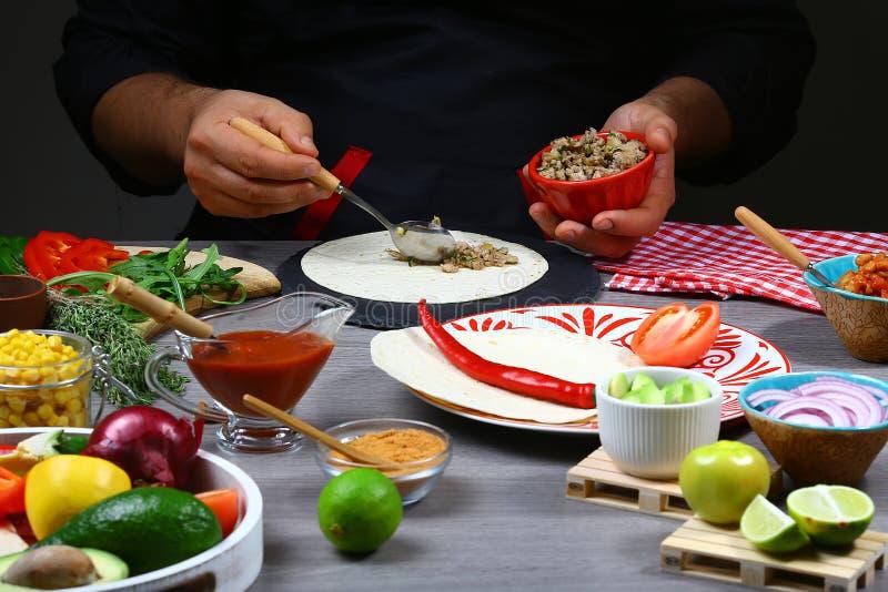 Szefa kuchni kulinarny meksykański burrito Szef kuchni wręcza opakunkowego burrito plombowanie w tortilla Proces narządzania meks obrazy stock
