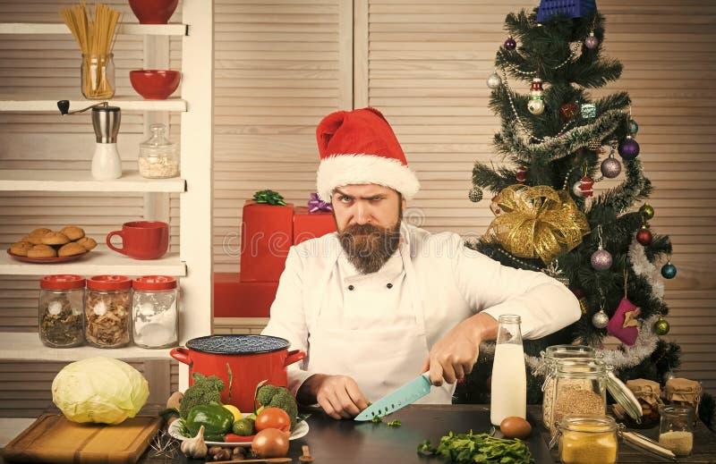 Szefa kuchni mężczyzna w Santa Claus kapeluszu kucharstwie zdjęcie royalty free