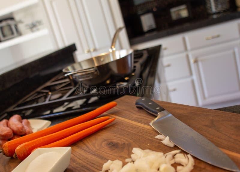 Szefa kuchni nóż na drewnianym cutten deskę z cebulą, marchewkami i sault siekającymi, Surowa kiełbasa przygotowywał piec na gril zdjęcia stock
