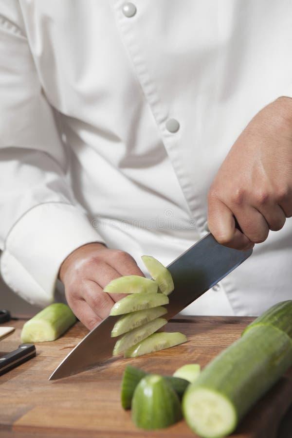 Szefa kuchni przecinania ogórek Na ciapanie desce fotografia royalty free