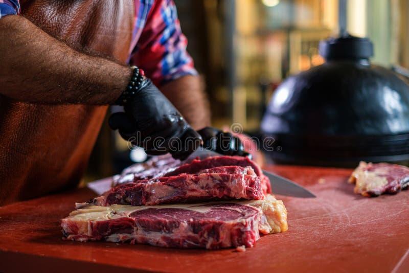 Szefa kuchni rozcięcia wołowiny steakes w restauracji fotografia stock