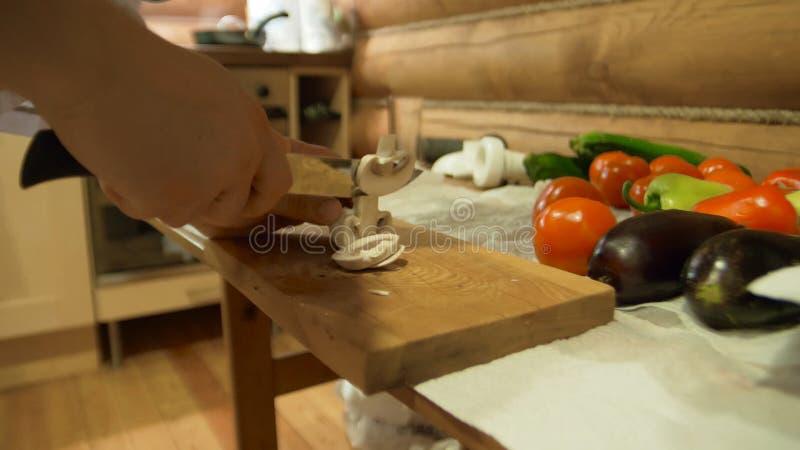 Szefa kuchni ` s ręki Mężczyzna sieka warzywa w biel ubraniach Świeży pieprz, pomidor, ogórek i zieleń na tle, fotografia royalty free