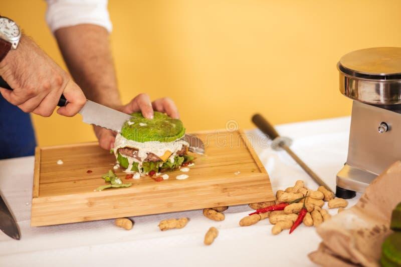 Szefa kuchni tnący hamburger w dwa halfs wykonywać ilość składniki obrazy royalty free