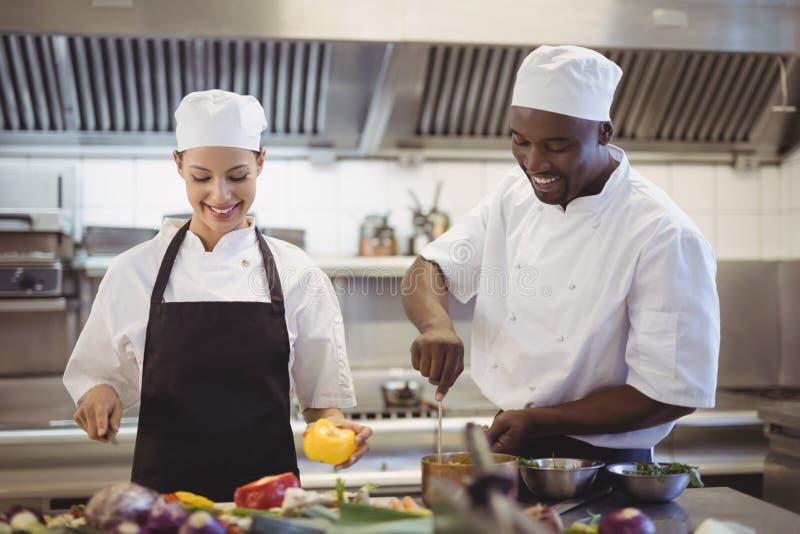 Szefowie kuchni przygotowywa jedzenie w handlowej kuchni zdjęcie stock