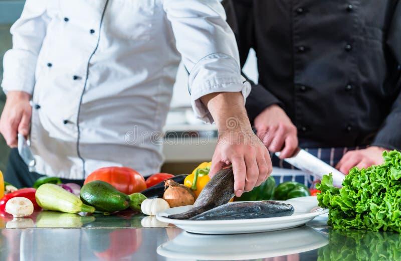 Szefowie kuchni przygotowywa jedzenie w pracie zespołowej przy restauracyjną kuchnią obraz stock