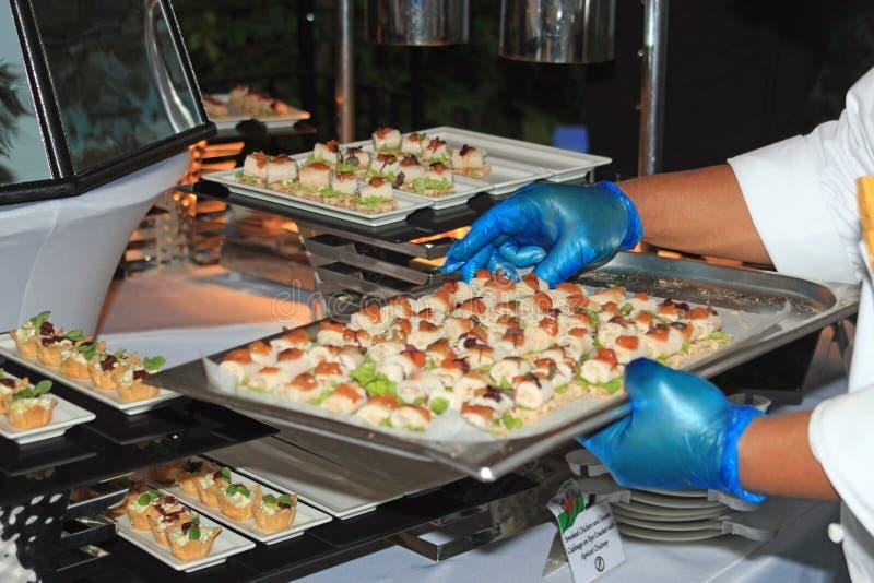 Szefowie kuchni układa canapés przy przyjęciem, przyjęciem, ślubem lub świętowaniem, zdjęcia royalty free