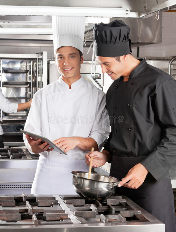 Szefowie kuchni Z Cyfrowego komputeru Kulinarnym jedzeniem fotografia royalty free
