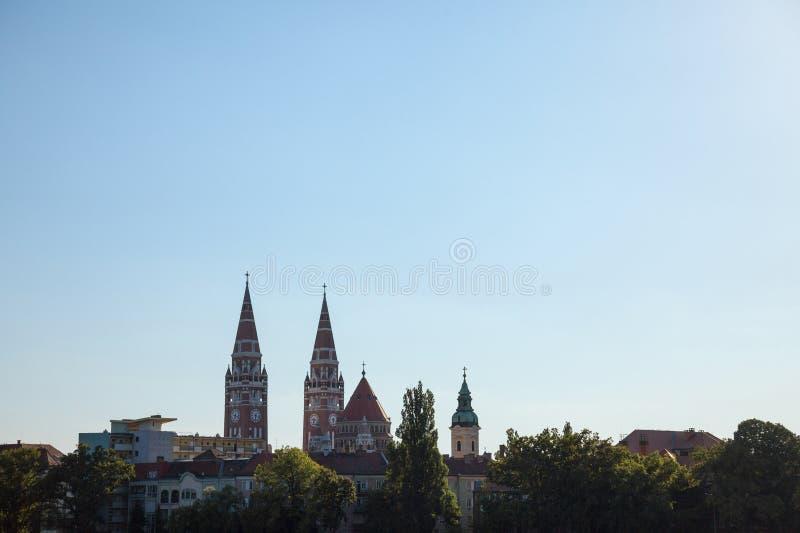 Szeged centrum, med en viktig på den Szeged domkyrkan som ses in i ljuset under solnedgång i sommar royaltyfri fotografi