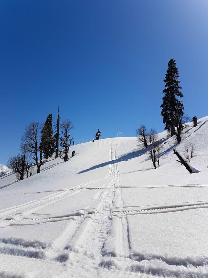 Szene des Schneeberges mit schneiden Bahnen des Schneemobil fahrung stockfotografie