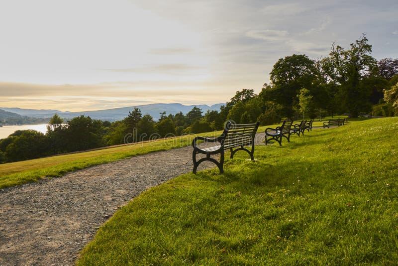 Szenische Abendansicht des Balloch-Schloss-Nationalparks mit historischen Bänke und des Loch Lomond in Schottland, Vereinigtes Kö lizenzfreie stockfotos