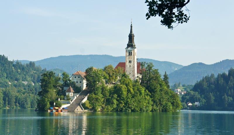 Szenische Ansicht über den See geblutet, Julian Alps und Kirche auf der Insel, sonniger Tag, geblutet, Slowenien stockfotografie