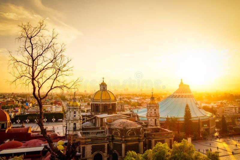 Szenische Ansicht an der Basilika von Guadalupe mit Mexiko- Cityskylinen bei Sonnenuntergang lizenzfreies stockfoto