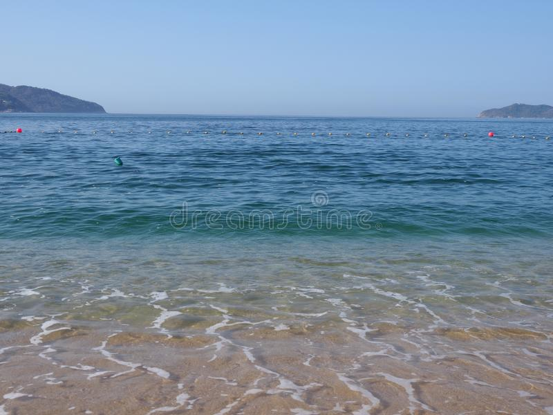 Szenische Ansicht des sandigen Strandes an der Buchtlandschaft von ACAPULCO-Stadt in Mexiko und von Wellen von Pazifischem Ozean stockfotografie