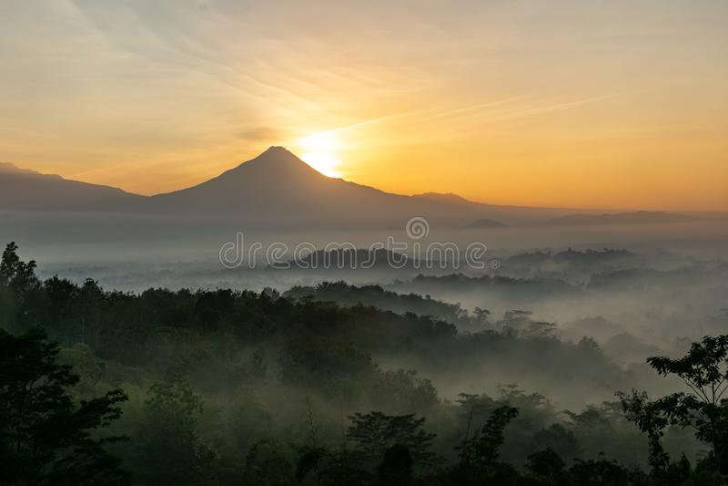 Szenische Ansicht des Sonnenaufgangs hinter Merapi-Vulkan, nebelhaftem Dschungel und Borobudur-Tempel in Indonesien lizenzfreie stockbilder