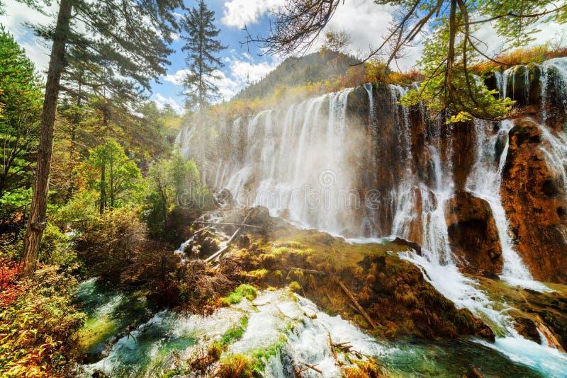Szenische Ansicht Nuo Ri Lang Waterfalls (Nuorilang) unter Holz stockfoto