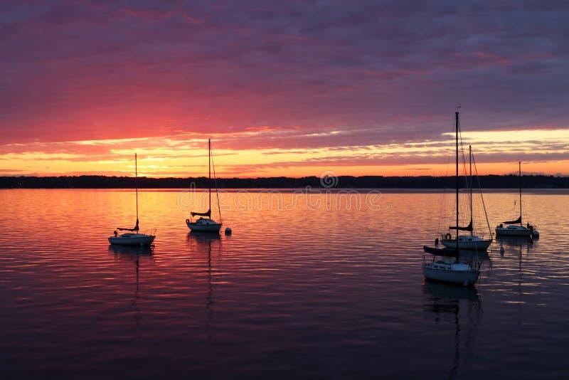 Szenische Ansicht von silhouettierten Yachten gegen buntes nach Sonnenuntergang stockfotografie