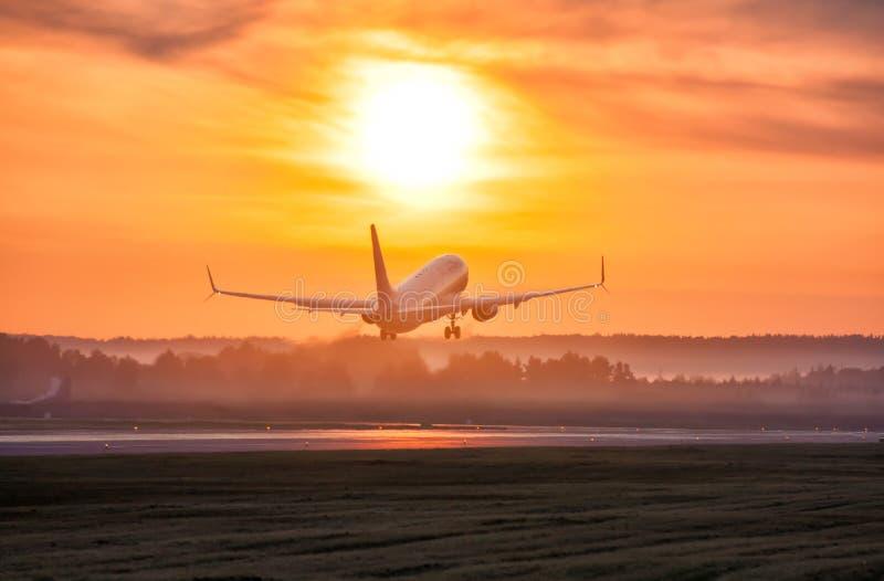Szenische Dämmerung mit einem Nebel am Flughafen Start eines Passagierflugzeuges stockbilder