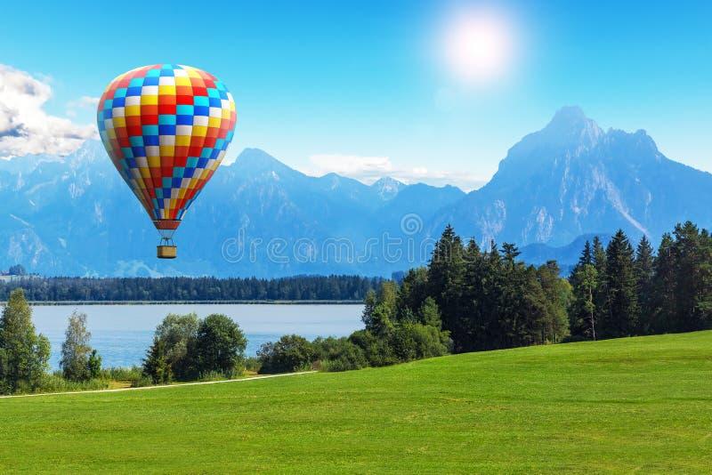 Szenische Sommerlandschaft mit Heißluftballon, -see und -bergen lizenzfreie stockfotos