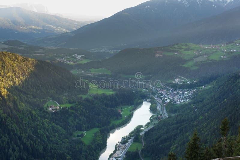Szenische Vogelperspektive auf Dörfern in den Dolomit mit Bergen in den Wolken auf Hintergrund und in den Wiesen auf Vordergrund lizenzfreie stockfotos