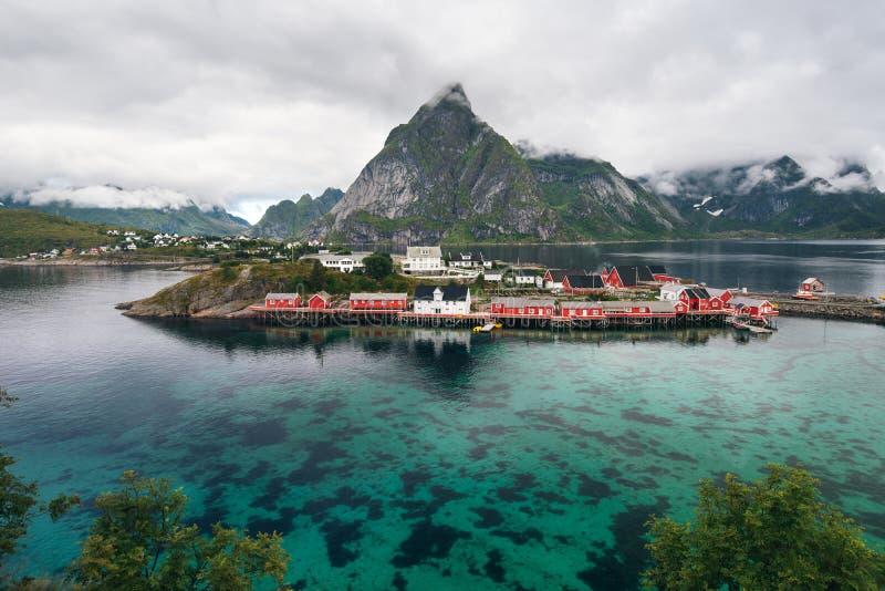 Szenischer Fjord auf Lofoten-Inseln mit typischer roter Fischenhütte und sehr hohen Bergspitzen lizenzfreie stockbilder