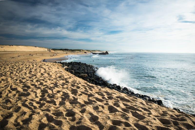 Szenischer sandiger Strand auf atlantischer Küstenlinie mit brechenden Wellen im blauen Himmel stockbild