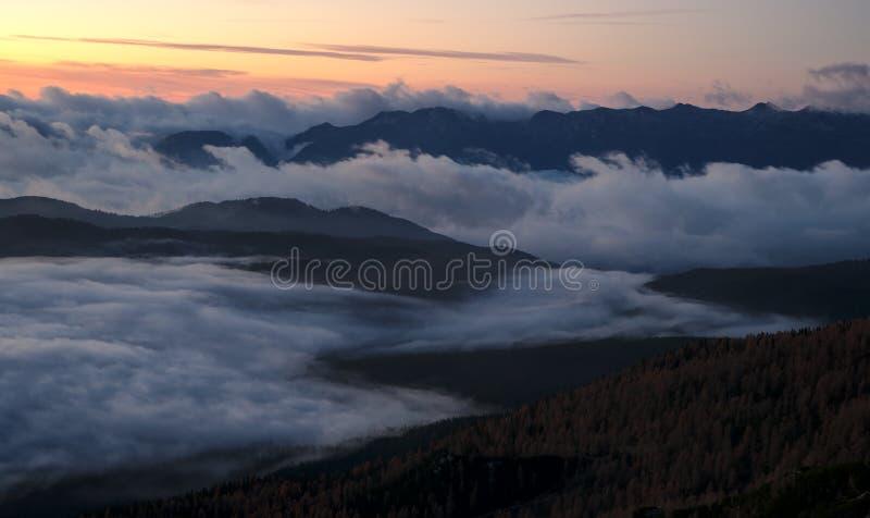 Szenischer Sonnenaufgang über nebelhafter Landschaft in den Bergen stockbilder