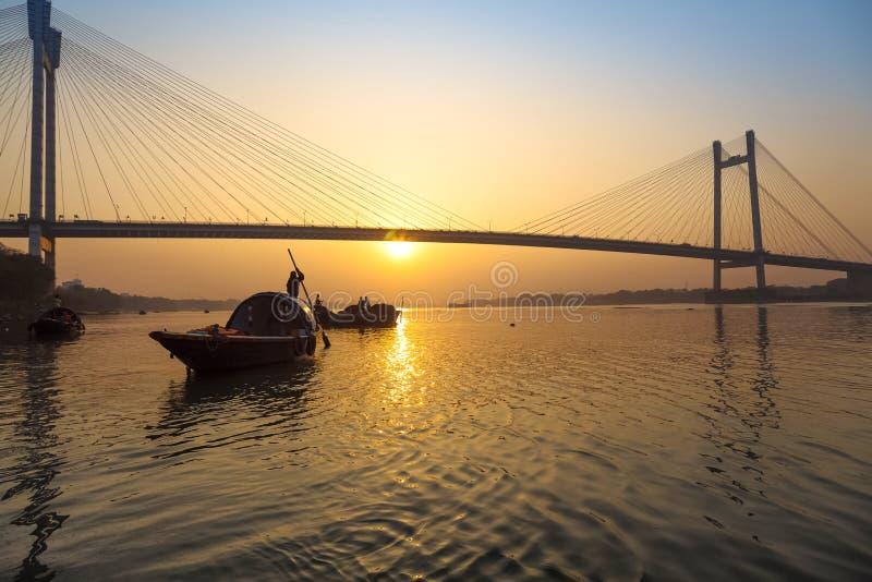Szenischer Sonnenuntergang über Vidyasagar-Brücke mit hölzernen Booten auf Fluss Hooghly, Kolkata, Indien lizenzfreie stockfotos