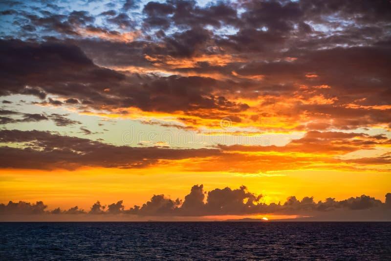 Szenischer Sonnenuntergang auf karibischem Meer mit dunklen Wolken gegen eine Orange und Blu Sky Schöner Hintergrund lizenzfreies stockfoto