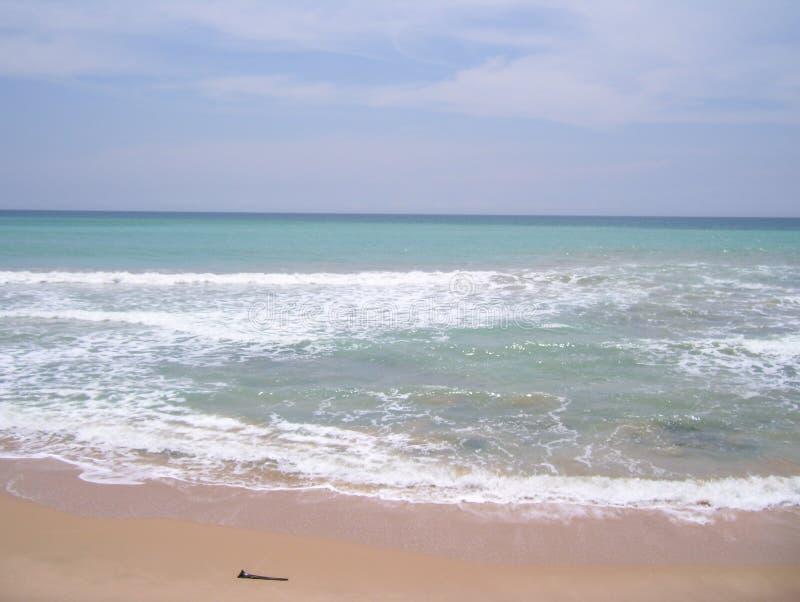 Szenischer Strand mit Leuchtstofftürkisblau-Meerwasser und weißen schäumenden Wellen stockbilder