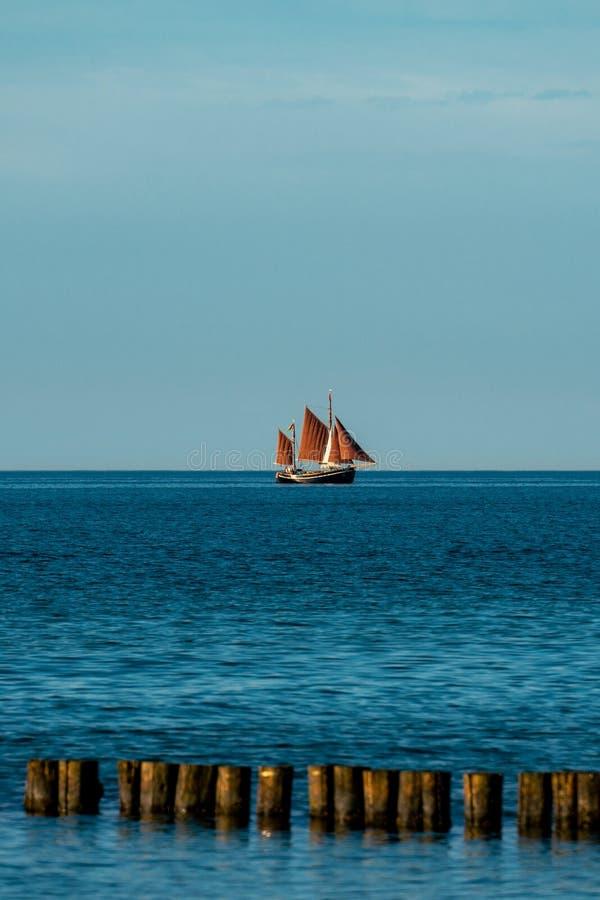 Szenisches Ozeanbild mit einem Segelboot mit braunen Segeln stockfotografie