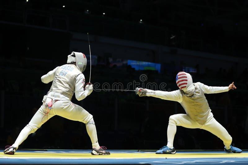 Szermierz Stany Zjednoczone drużyna R współzawodniczy przeciw drużynowemu Egipt szermierzowi w mężczyzna ` s drużyny folii Rio 20 zdjęcia royalty free