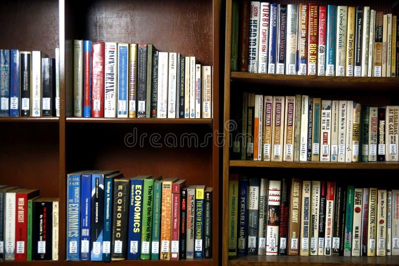 Szeroka rozmaitość książki na drewnianych półkach wśrodku biblioteki obraz royalty free