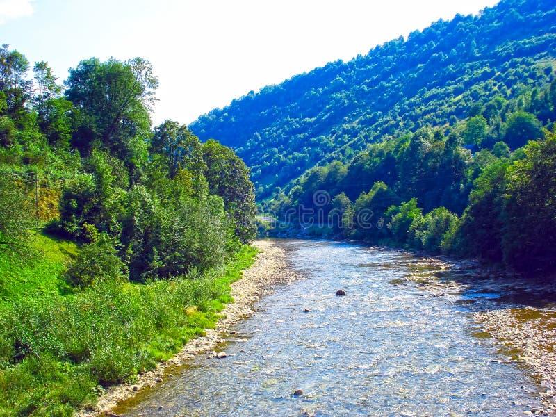 Szeroka rzeka która kłama w halnej dolinie Góry blisko rzeki zakrywają z lasami fotografia royalty free