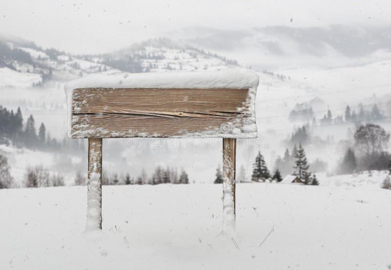 Szeroki drewniany kierunkowskaz z śniegiem i górami zdjęcie stock