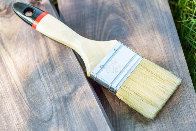 Szeroki farby mu?ni?cie k?ama na drewnianej desce na zielonej trawie w ulicie w g?r? bia?a farba p?dzel odizolowane zdjęcia stock