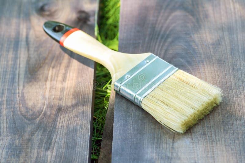 Szeroki farby mu?ni?cie k?ama na drewnianej desce na zielonej trawie w ulicie w g?r? Farby mu?ni?cie na drewnianym tle obraz royalty free