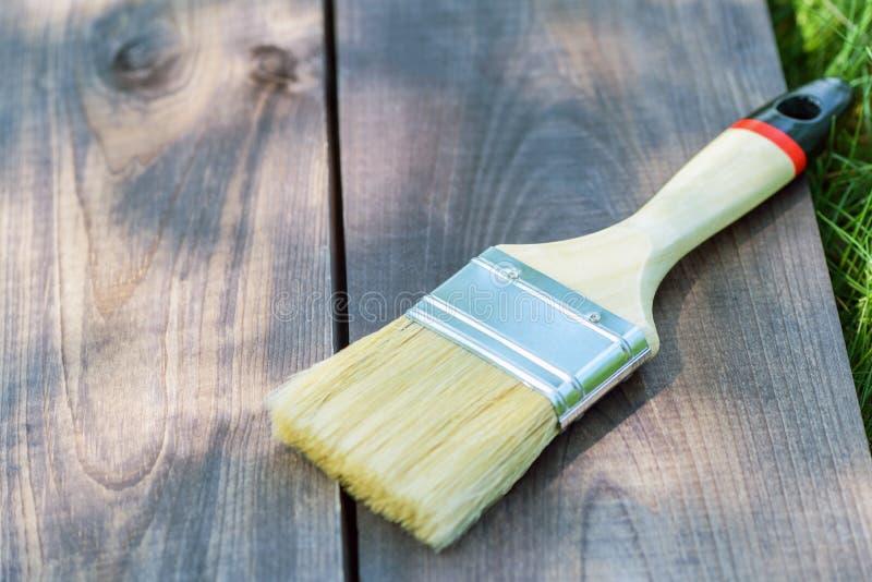 Szeroki farby mu?ni?cie k?ama na drewnianej desce na zielonej trawie w ulicie w g?r? Farby mu?ni?cie na drewnianym tle obraz stock