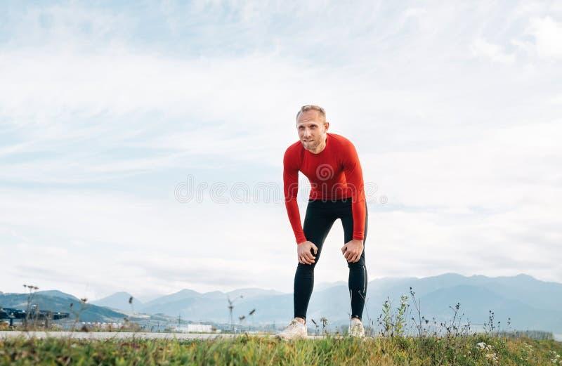 Szeroki kąta krótkopęd mężczyzna ubierał w czerwień długiego rękawa koszulowy bardzo zmęczonym po jog drogą z halnym tłem i obraz stock