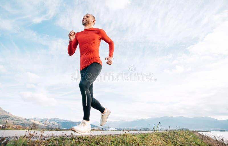 Szeroki kąta krótkopęd mężczyzna ubierał w czerwień długiego rękawa koszulowych bieg drogą z halnym tłem obrazy stock