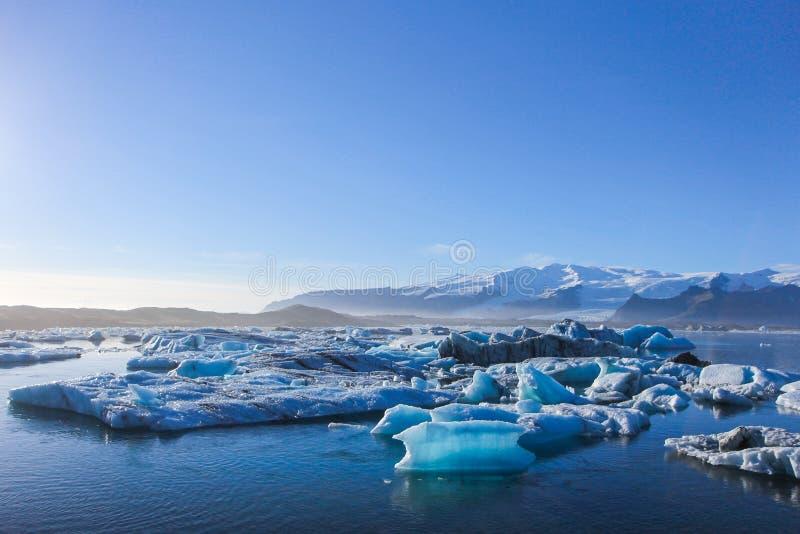 Szeroki krajobraz góry lodowa unosi się na wodzie pod bardzo jasnym niebieskim niebem z kopii przestrzenią zdjęcia royalty free