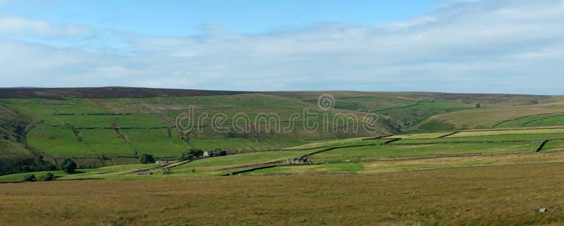 Szeroki panoramiczny widok Yorkshire dolin krajobraz z polami i domami wiejskimi ogradzającymi kamiennymi ścianami z otwartym moo obraz royalty free