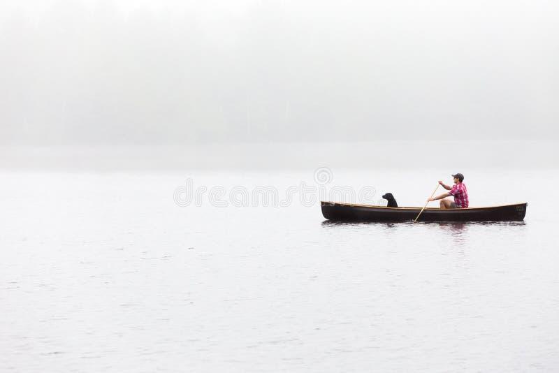 Szeroki strzaÅ' samca z czarnym psem na jeziorze zdjęcie royalty free