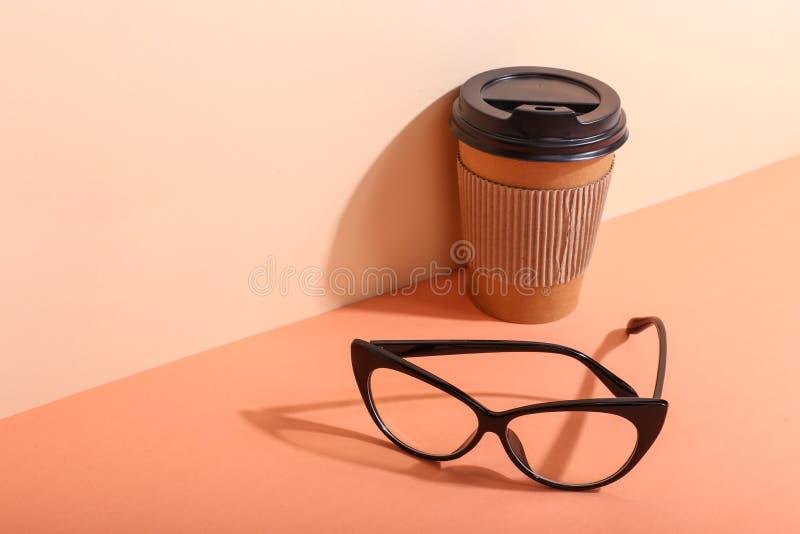 Szkła i papierowa filiżanka z kawą na pomarańczowym tle, ranek są twardym cieniem od słońca zdjęcia stock