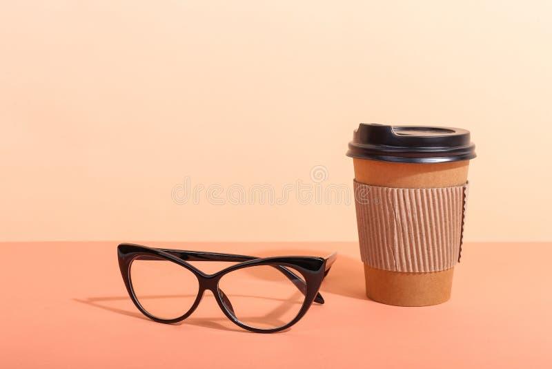 Szkła i papierowa filiżanka z kawą na pomarańczowym tle, ranek są twardym cieniem od słońca obraz stock